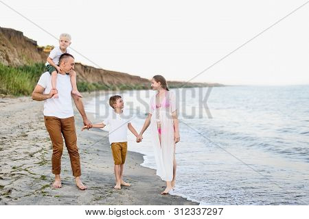 Family Of Four Walking Along The Seashore. Parents And Two Sons. Happy Friendly Family