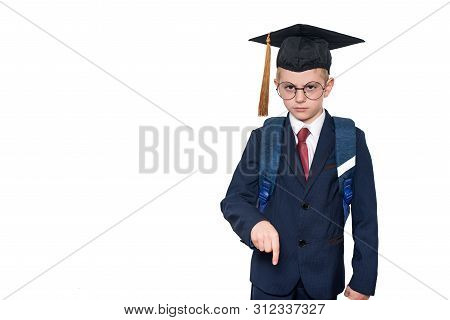 Serious Schoolboy In A Suit, Glasses And An Academic Hat Is Pointing Down. School Concept. Isolate