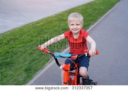 Portrait Of A Handsome Blond Boy Rides On A Children's Bicycle. Urban Background