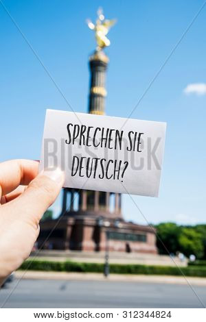 closeup of the hand of a young caucasian man showing a speech bubble with the question sprechen sie deutsch, do you speak german written in german, in front of the Victory Column in Berlin, Germany poster