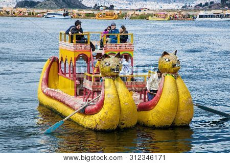 Uros, Peru - Jan 5, 2019. Tourists travel by Traditional Totora boat on Uros floating islands at Titicaca lake i, Puno, Peru, South America.