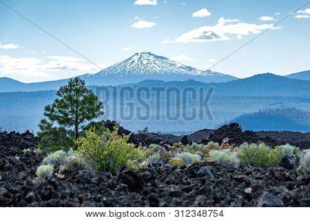 View Of Mt. Bachelor From Newberry Volcano National Monument. Black Lava Rocks, Trees And Desert Veg