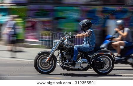 Bucharest, Romania - June 27, 2019: A Harley-Davidson Fat Boy chopper motorcycle passes with speed  through the Gheorghe Magheru Boulevard in Bucharest, Romania. This Image is for editorial use only