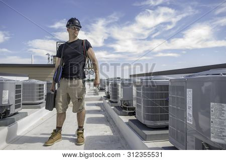 Hvac Technician Standing Inbetween 2 Rows Of Condensers, Holding Gauges And Other Hvac Tools