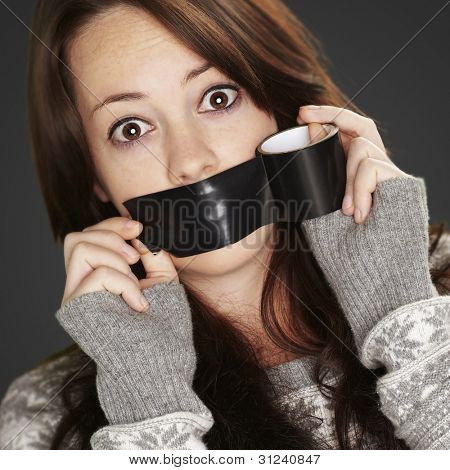 portrait of scared girl being silenced by herself over black background