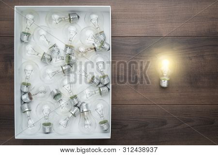 Lightbulb Glowing Outside The Box. Top View Image Of Thinking Out Of The Box Concept. Conceptual Pho