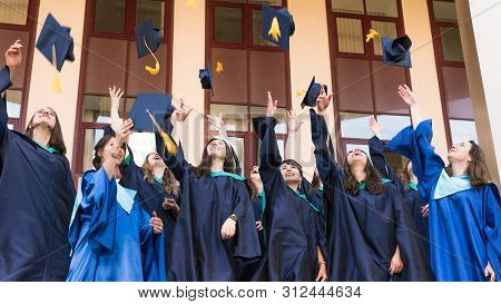 University Graduates  Throwing Graduation Hats In The Air. Group Of Happy Graduates In Academic Dres
