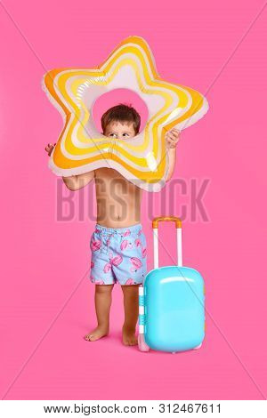 Cute Little Boy With Inflatable Ring And Blue Suitcase On Pink Background