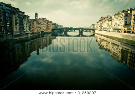 Cross processed view of ponte vecchio with reflection on the arno river