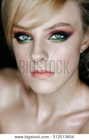 Serious Gaze Young Woman with Green and Brown Eyes Shadow, Natural Color Lips Style Face Painting. Modern Make-up Girl with Blonde Short Hair Posing on Black Background Studio Portrait Closeup Photo poster