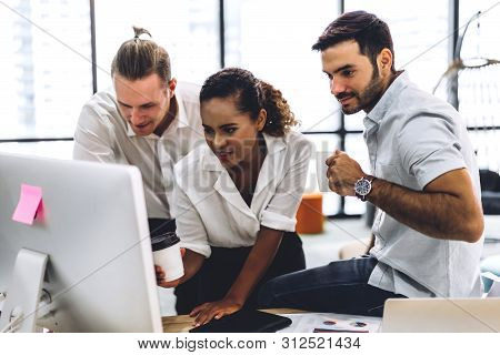 Group Of Casual Business Working Discussing Strategy And Documents With Desktop Computer.creative Bu
