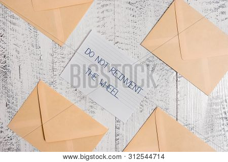 Text sign showing Do Not Reinvent The Wheel. Conceptual photo stop duplicating a basic method previously done Four envelopes around ruled paper sheet old wooden vintage background. poster