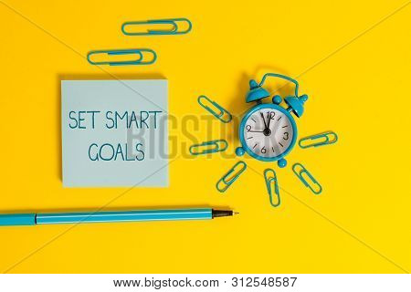 Word writing text Set Smart Goals. Business concept for giving criteria to guide in the setting of objectives Metal alarm clock wakeup clips ballpoint notepad colored background. poster