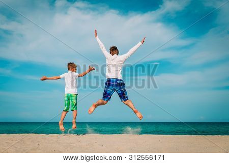Father And Son Have Fun Jump At Tropical Beach