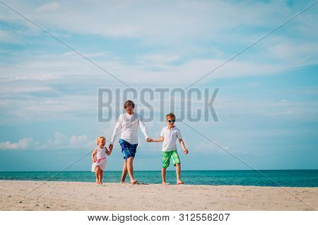 Happy Father And Two Kids Walking On Beach