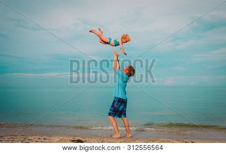 Father And Happy Cute Little Daughter Play At Sky On Beach