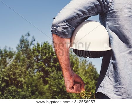 Engineer, Holding White Hardhat In The Park