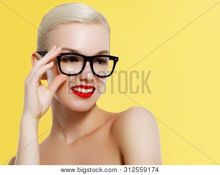 Fashion And Accessories. Model Girl Isolated Over Yellow Background. Beauty Stylish Blonde Woman Pos