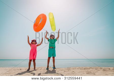 Happy Boy And Girl Play With Floaties On Beach Vacation
