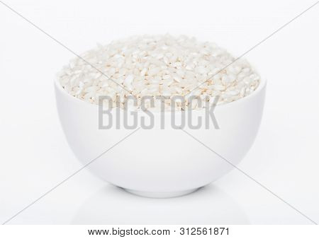 White Bowl Of Raw Organic Arborio Risotto Rice On White Background.