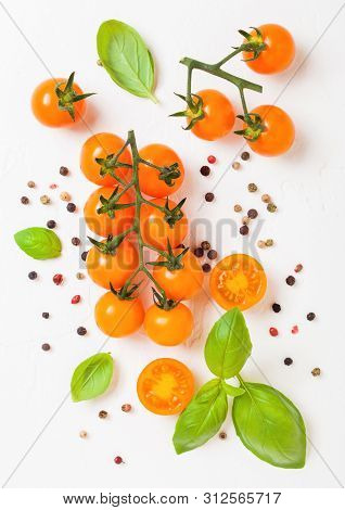 Organic Cherry Orange Rapture Tomatoes On The Vine With Basil And Pepper On White Kitchen Stone Back