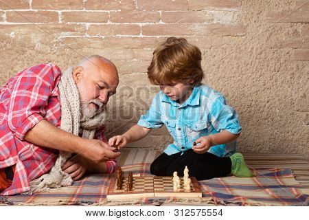 Cute Boy Developing Chess Strategy. Senior Man Thinking About His Next Move In A Game Of Chess. Ches