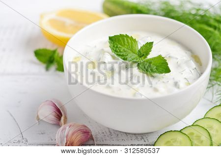 Greek Dip Sauce Or Dressing Tzatziki And Ingredients Decorated With Olive Oil And Mint On White Wood