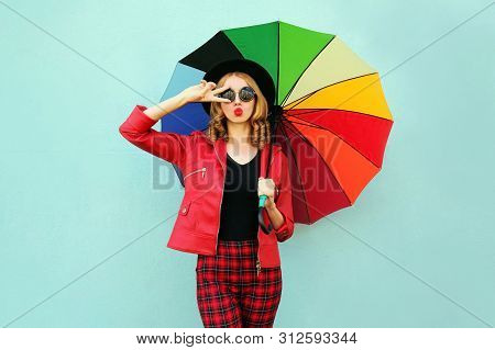 Stylish Young Woman With Colorful Umbrella Blowing Red Lips Sending Sweet Air Kiss, Wearing Red Jack