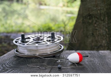 Fishing Reel With Fishing Line, Red And White Float, Hook And Sinker On Wooden Table On Natural Back