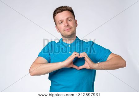 Handsome Man In Blue Shirt Making A Heart With His Hands