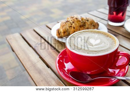 Red Cup Of Cappuccino With Croissant On A Table In An Outdoor Cafe. Tipical Italian Breakfast. Selec