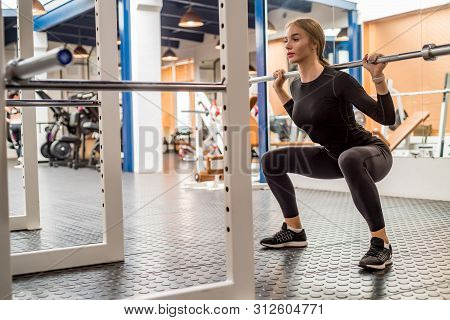Young Woman Does Barbell Squats In Modern Gym