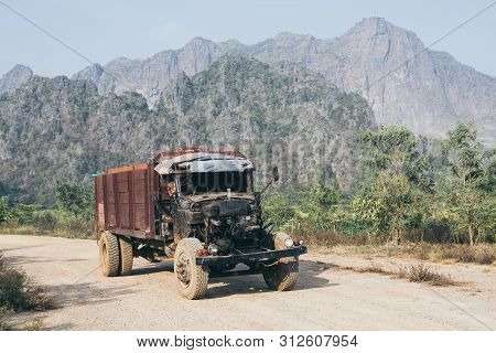 Old Truck Driving On The Dirt Road With Zwegabin Mountain On Background In Hpa-an, Myanmar.