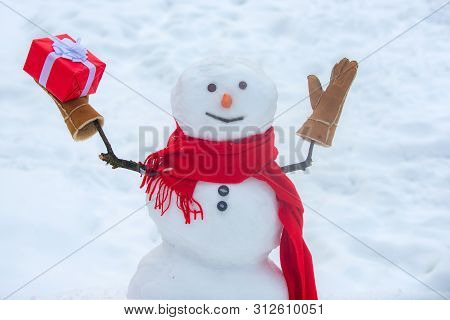 Happy Snowman With Christmas Gift Standing In Winter Christmas Landscape. Snowmen - Gift Presents Co