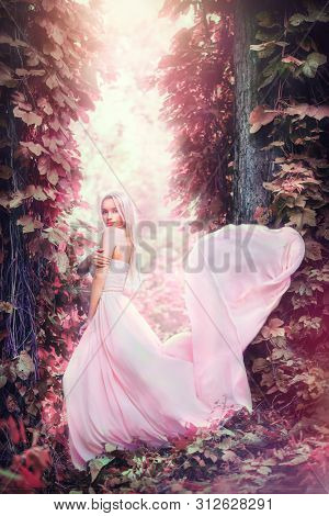 Beauty romantic young woman in long chiffon dress with gown posing in the fantasy forest on sunset. Beautiful happy bride model girl enjoying nature outdoors, fluttering dress