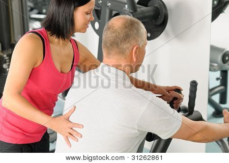 Active man watch personal trainer adjust machine level at gym