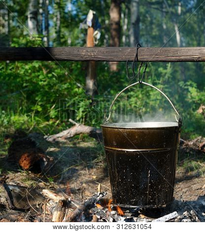 In A Bucket Hanging On A Stick Over A Fire, Soup Is Cooked In The Wild Northern Forest Of Yakutia At