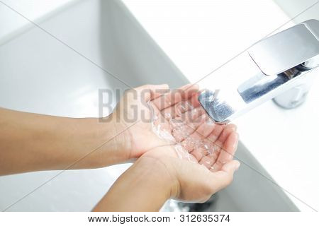 Closeup Woman's Hand Holding Water For Cleaning In Bathroom, Selective Focus