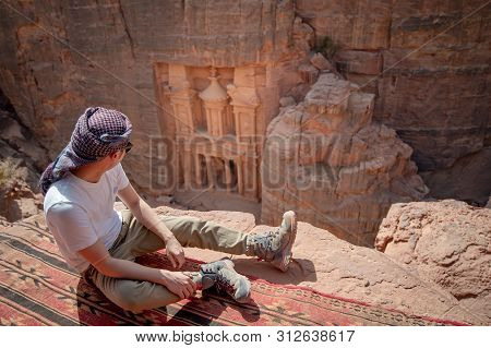 Asian Man Traveler Sitting On Carpet Viewpoint In Petra Ancient City Looking At The Treasury Or Al-k