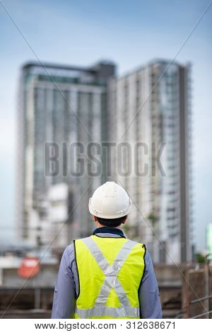 Asian Maintenance Worker Man With Safety Helmet And Green Vest Standing At Construction Site. Civil