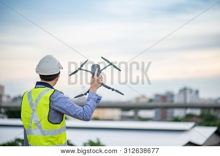 Asian Engineer Man Holding Drone At Construction Site. Male Worker Using Unmanned Aerial Vehicle (ua