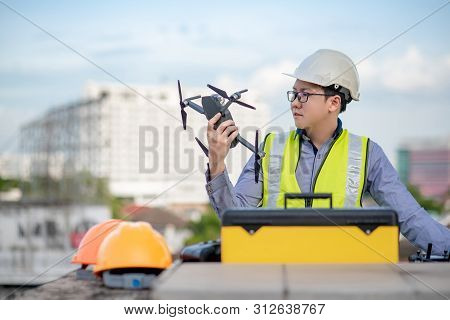 Asian Engineer Man Working With Drone And Working Tools At Construction Site. Male Worker Using Unma