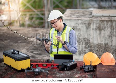 Asian Engineer Man Working With Drone, Laptop And Working Tools At Construction Site. Male Worker Us