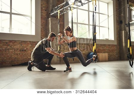 Doing Squat Exercise. Confident Young Personal Trainer Is Showing Slim Athletic Woman How To Do Squa