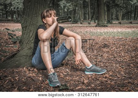 Unhappy Woman Drinking Wine In The Park And Sitting Under Tree - Alcoholism Concept