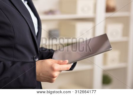 Business woman below chest using tablet in a homey environment