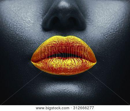 Lips Makeup art, black skin and Gold lips, golden lipgloss on sexy lips, golden lipstick. Beautiful model girl's mouth, black skin. Make-up. Beauty dark face makeup close up. African American