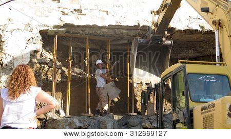 Alora, Spain - July 5, 2019: Excavator Demolishing Old Residential Building In Andalusian Village