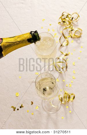 Champagne Bottle Fills Glasses On Party Table