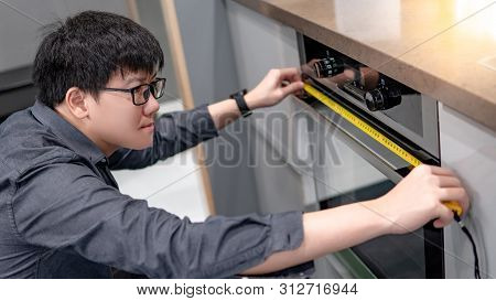 Asian Man Interior Designer Using Tape Measure On Oven In The Kitchen Showroom In Furniture Store. H